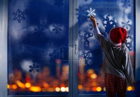Little kid in Santa hat touching snowflake on frosty window on Christmas eve