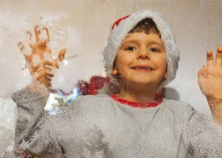Nice little boy in Santa hat looking through the frosty window with snowflakes