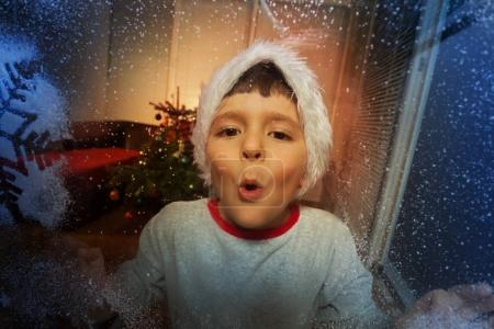 Little boy blows on the frosty winter window with frozen snowflakes on New Year day in Santa hat