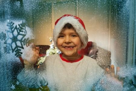 Portrait of little happy boy looking though frosty window in santa hat with painted snowflakes on the glass
