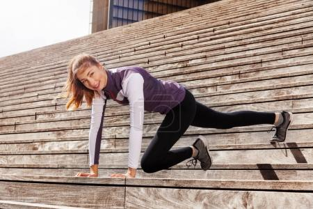 Happy young sportswoman exercising outdoors on city stairs