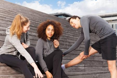 Two young women and man in sportswear stretching before training outdoors on staircase