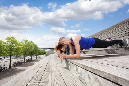 Side view of sporty young people doing plank exercise outdoors on city stairs