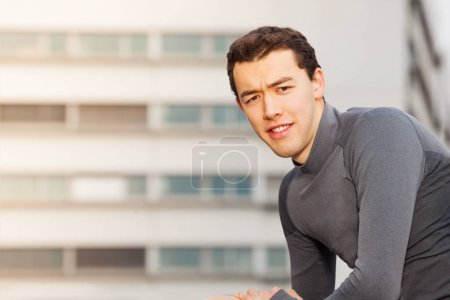 Portrait of handsome Asian sportsman in tracksuit looking at camera, standing against building with copy-space