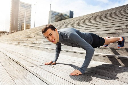 Active young man doing push-up exercises outdoors on city stairs