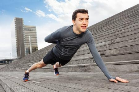 Handsome sporty man in grey tracksuit doing push-ups on one hand outdoors in the city