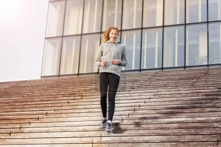 Full-length portrait of happy young woman in sportswear going downstairs as part of her workout outdoors on city stairs