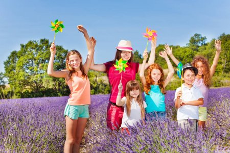 Photo for Group of happy preteen kids playing with multicolor pinwheels in lavender field at sunny day - Royalty Free Image