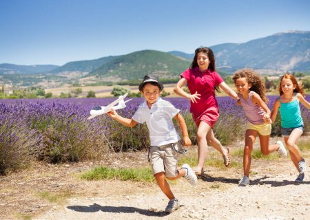 Three girls hurry after boy holding toy plane outdoors in summer