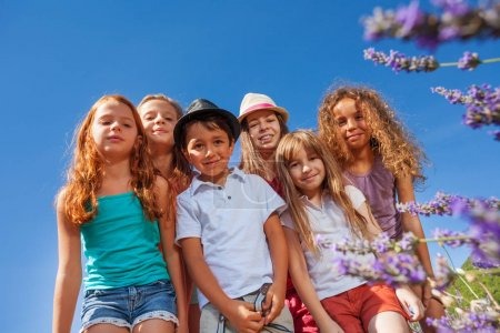 Photo for Bottom view picture of happy preteen children standing together in lavender field against clear sky and looking at camera - Royalty Free Image