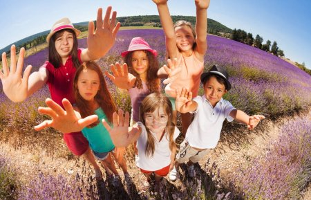High angle shot of six age-diverse kids standing in lavender field in summertime and reaching out their hands to camera