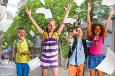 Group of kids throwing paper in the air laughing and lifting hands happy after school