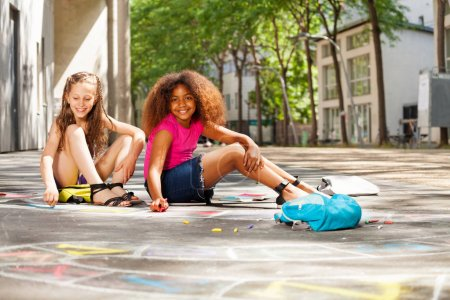 Two girls draw numbers for hopscotch game on the street