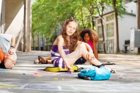 Portrait of a girl with friends draw numbers for hopscotch game on the street