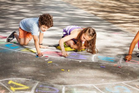 Group of kids draw with chalk on the asphalt floor
