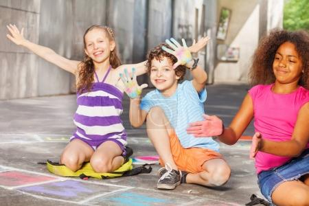 Group of kids sitting and drawing hopscotch game showing colored palms