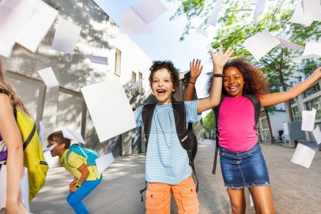 Happy very exited boy throwing papers in the air with friends near the school door