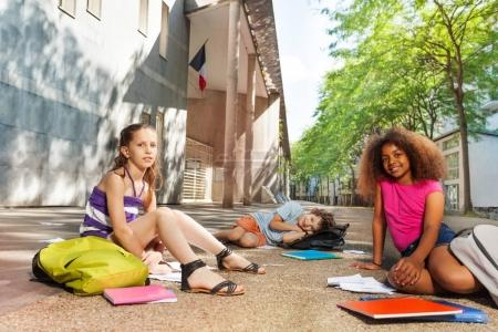 Group of kids sit on the ground with textbooks and books near school