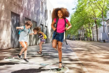 Portrait of kids jumping on the hopscotch squares and letters looking at camera with African girl on foreground