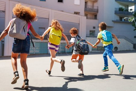 Group of kids run together holding hands and wearing backpacks toward school