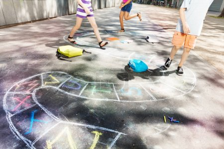 Hopscotch game drawn with chalk on the road asphalt and kids jump on background
