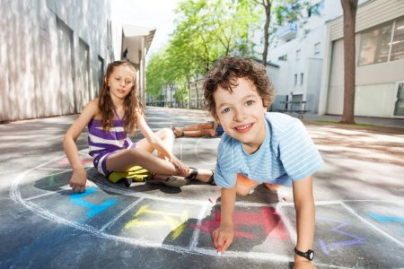 Happy boy and friends draws with chalk hopscotch game on the asphalt in the school yard smiling