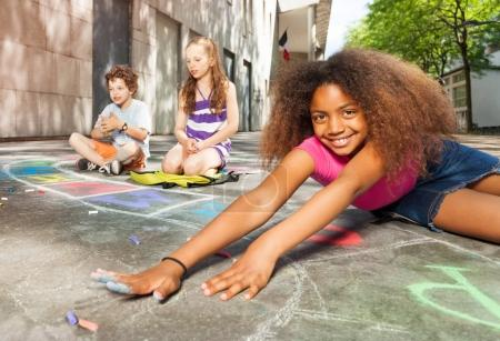 Group of kids draw with chalk on the yard and beautiful curly African girl stretch hands
