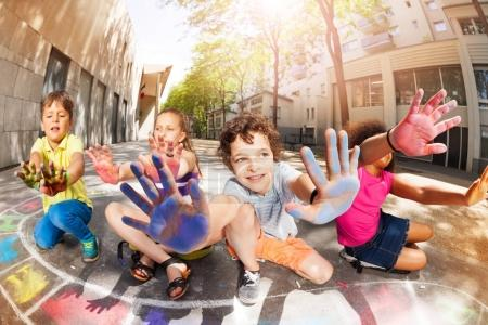 Photo for Group of kids with hands full of chalk showing palms and smiling drawing hopscotch - Royalty Free Image