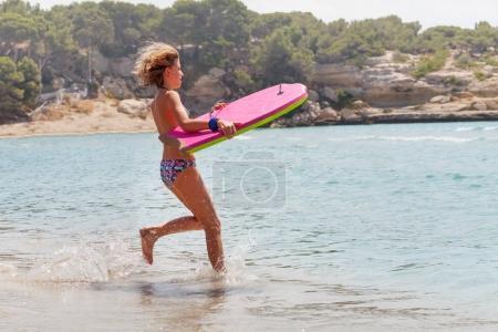 Beautiful blonde teen girl running to the sea with rose body board
