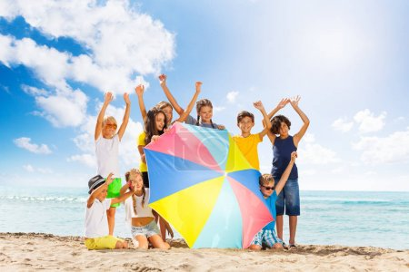 Many happy kids behind huge beach umbrella together on summer vacation with lifted hands on the sea