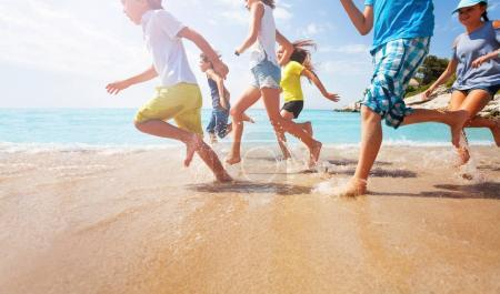 Close-up of multiple legs of kids running in shallow sea water with sunlit background