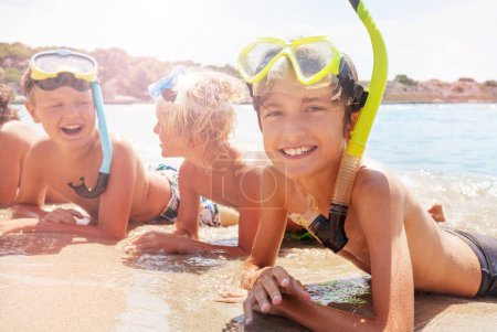 Boy with friends in scuba mask smiling laying on the sand and sea waves surge kids