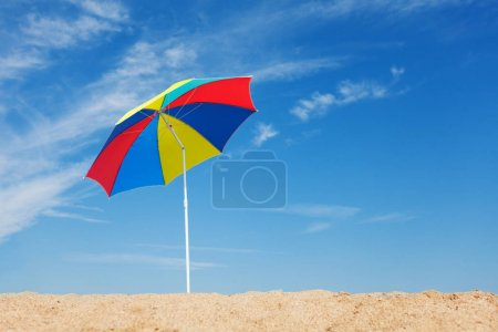 Opened multicolored beach umbrella against blue sky background at sunny day