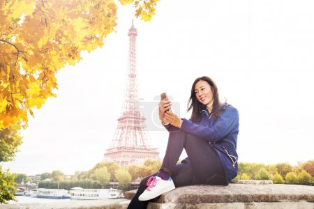 Happy young woman sitting on the embankment of Seine river with the Eiffel Tower on background and texting on smart phone