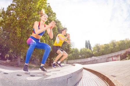 Happy athletes performing jumps during functional training and crossfit workout