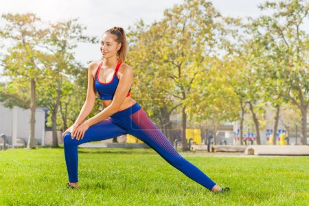 Photo for Young fitness woman stretching legs before workout outdoors - Royalty Free Image