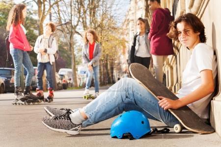 Photo pour Vue latérale d'un adolescent avec planche à roulettes et casque, assis sur le trottoir à côté de ses amis, regardant la caméra - image libre de droit