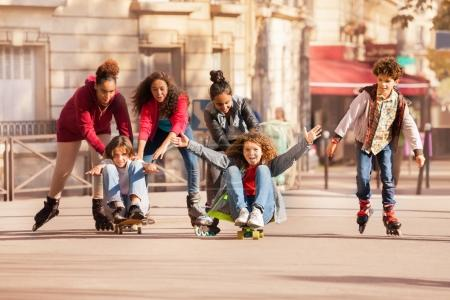 Group of happy teenagers having fun rollerblading and skateboarding during holidays