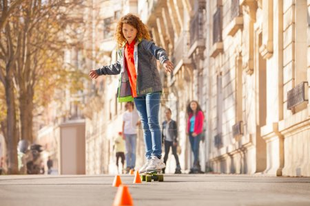 Teenage boy curving around the cones on skateboard at the side walk with friends