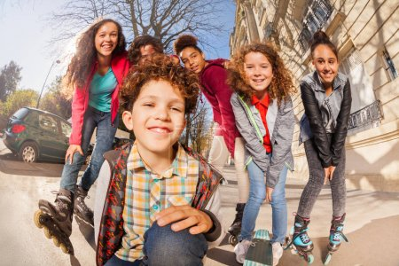 Multiethnic teenage boys and girls with inline skates or skateboards having fun at city streets