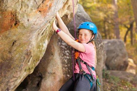 Portrait of teenage girl, happy mountaineer in helmet, training rock climbing outdoors