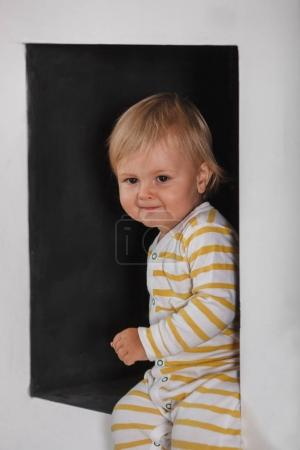 Photo for Portrait of smiling cute little boy wearing sleepwear in the black wall niche - Royalty Free Image
