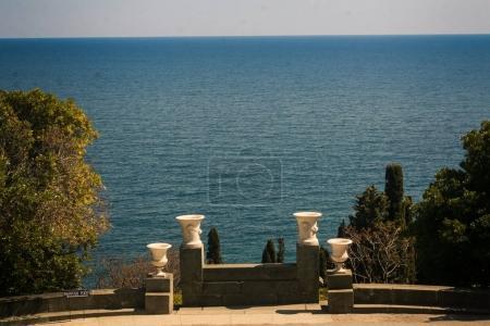 Vorontsov palace park marble vases under sunlight against azure sea in spring Crimea