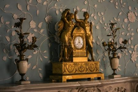 Vorontsov palace interior large old-aged bronze fireplace clock against wall decorated with fabric Crimea Ukraine