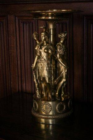 closeup Crimea Vorontsov palace interior bronze women sculpture candelabra against wooden wall
