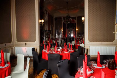 served tables in red, white and black colors with candlesticks and blue candles decorated with web imitation in gothic style catering service banquet
