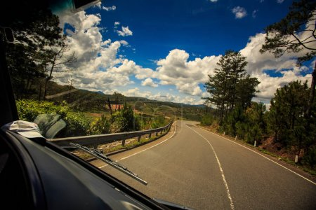 Photo pour Courbure de l'autoroute ensoleillée contre les terres de campagne boisées vallonnées et ciel nuageux bleu - image libre de droit