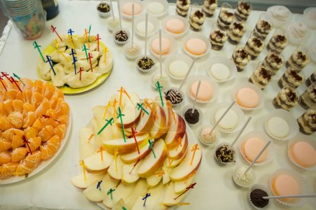 assorted fruits with skewers and tasty sweets served on white table