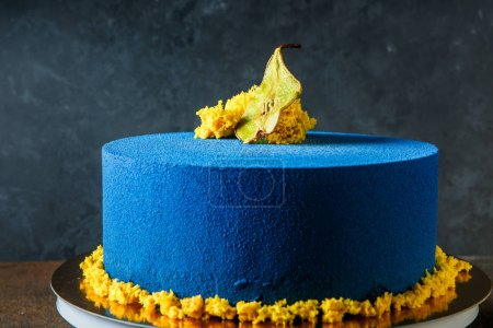 handmade blue round cake decorated with dried pear and pieces of yellow sponge cake
