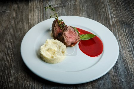 Photo for Tasty barbecued juicy meat pieces served with potato puree garnish and red sauce on white restaurant plate on dark wooden table - Royalty Free Image